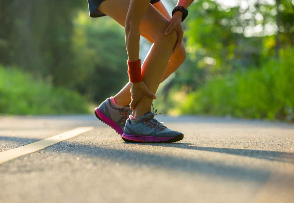Image of a Woman runner got sports injury running on forest trail