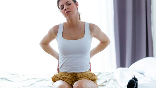 Image of a young woman with back pain sitting on the bed at home