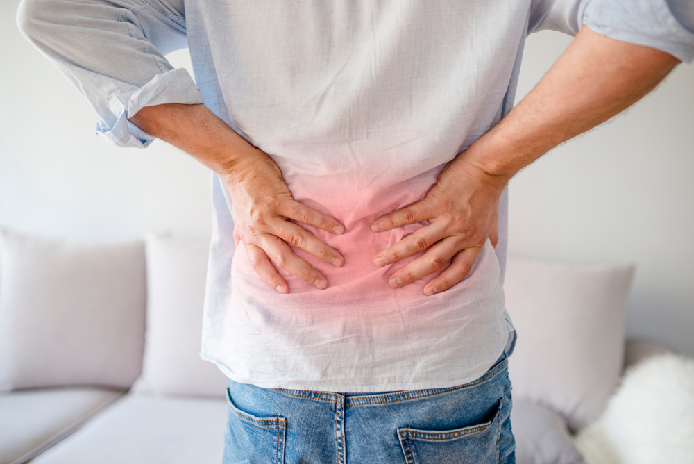 Image of a young man holding his back in pain