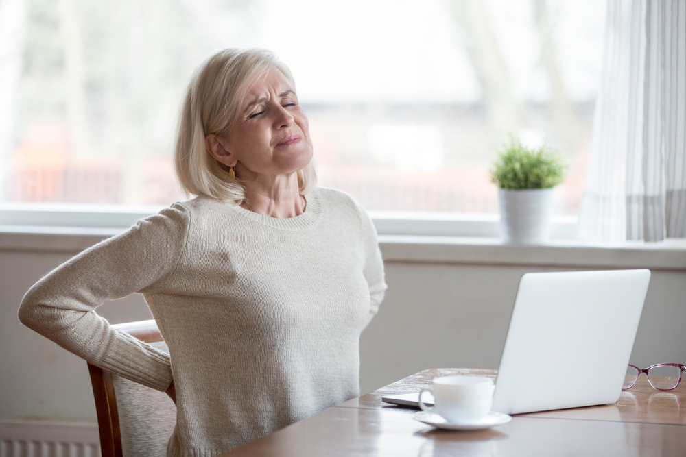 image of an Upset mature middle aged woman feels back pain