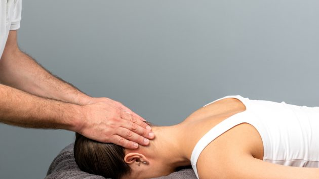 image of an osteopath doing manipulative neck and head massage on female patient