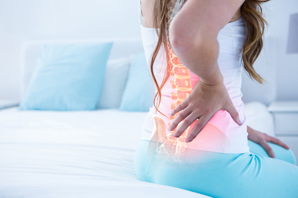 image of a Digital composite of highlighted spine of woman with back pain at home