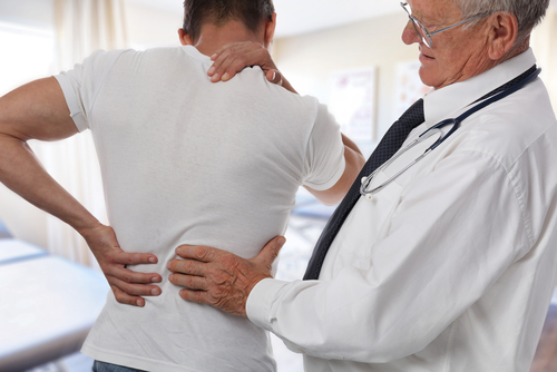 Image of a Male Doctor and patient suffering from back pain during medical exam