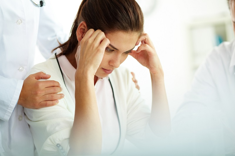 image of a woman with headache touching her temples with medical staff supporting her