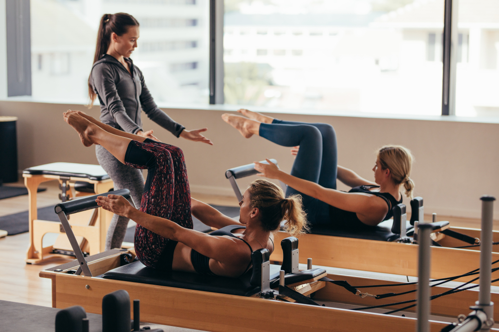 image of Women doing pilates exercises lying on pilates workout machines while their trainer guides them