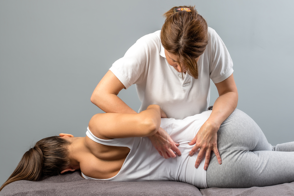 image of a Female physiotherapist doing manipulative spine treatment on young patient