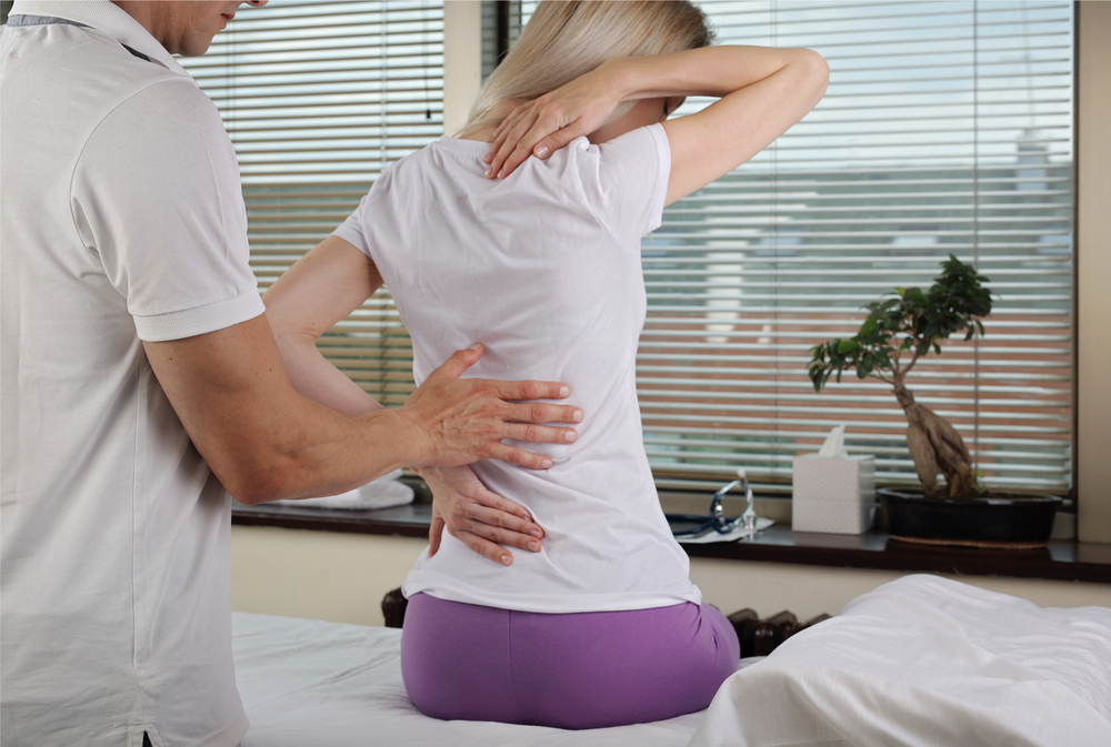 Image of a Woman patient suffering from back pain during medical exam