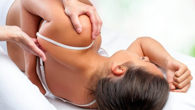Close up top view of osteopath doing healing treatment on female shoulder blade, Image by city osteopathy